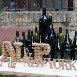 El lema de la boda con botellas de cava y vino, y tapones de corcho.