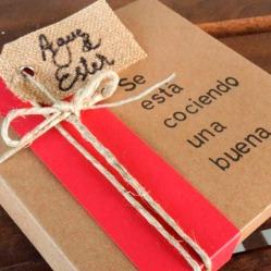 Cajita de presentación de la invitación: se está cociendo una buena... primera referencia a la afición de Mary! Los elementos eran una cajita hecha a medida, un fajín rojo y una tarjetita de ràfia caligrafiada atada con cuerda rústica.